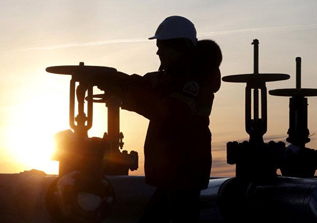 Un obrero revisa la válvula de un tubo de petróleo