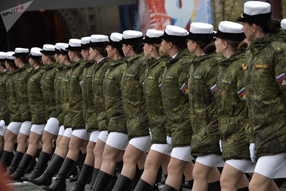 Mujeres cadetes visten chaquetas de invierno antes del inicio del desfile militar