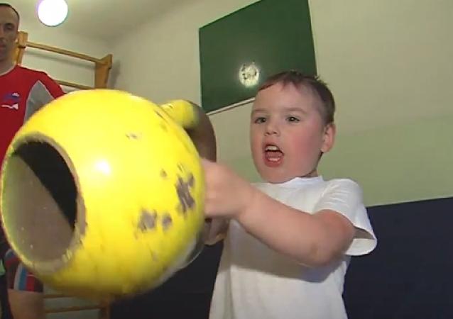 Un niño de 4 años levantando pesas