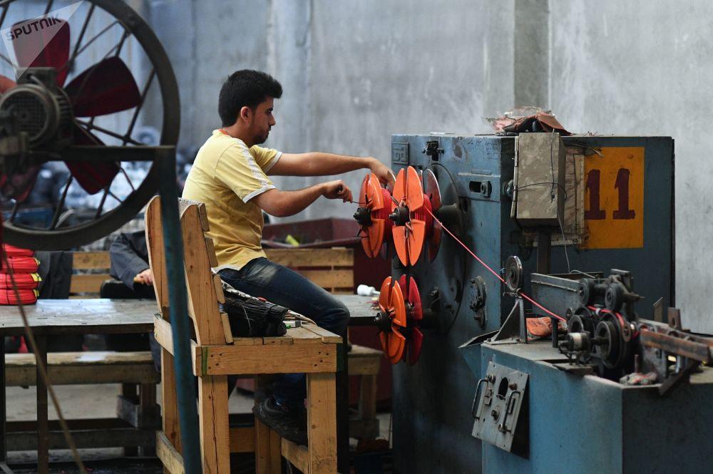 Obrero en el taller de la planta para la producción de cables eléctricos en los suburbios del sur de Damasco