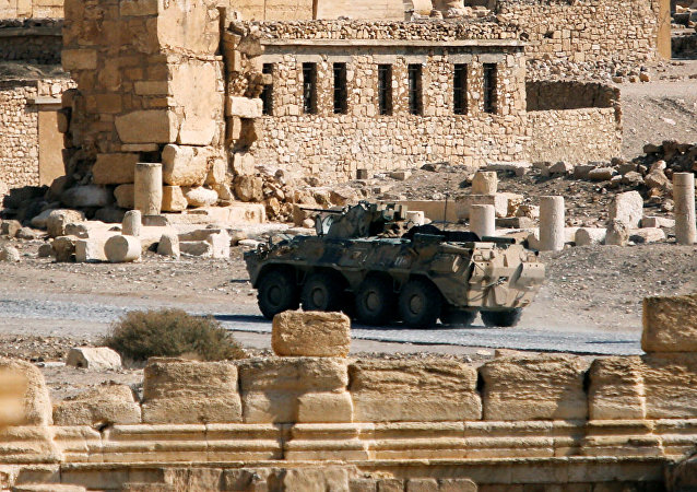 A Russian military vehicle drives near ruins in the historic city of Palmyra,
