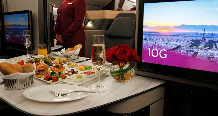 Azafata de Qatar Airways presenta asientos de la primera clase de un Boeing 777