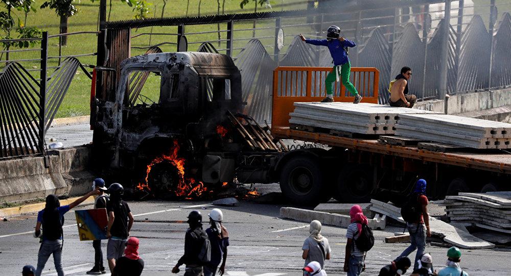 Manifestantes derriban la cerca de una base aérea en Venezuela