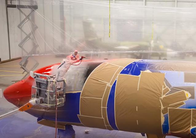 Operarios pintando un avión
