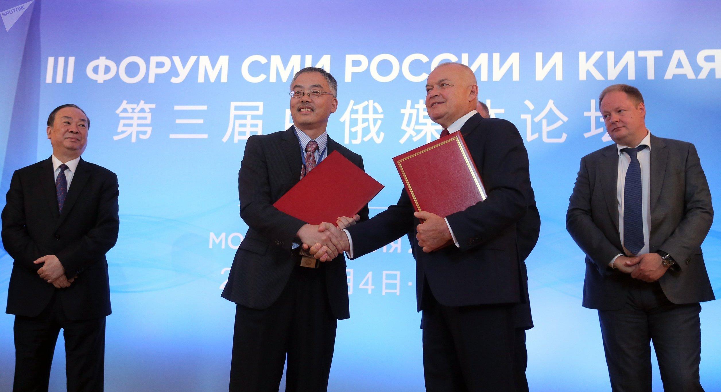 El vice redactor jefe de la agencia Xinhua, Zhou Zongming, y el director general de la agencia Rossiya Segodnya, Dmitri Kiseliov