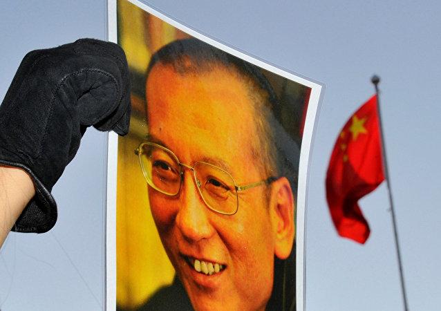 El retrato del disidente chino y premio Nobel de la Paz, Liu Xiaobo, y la bandera de China