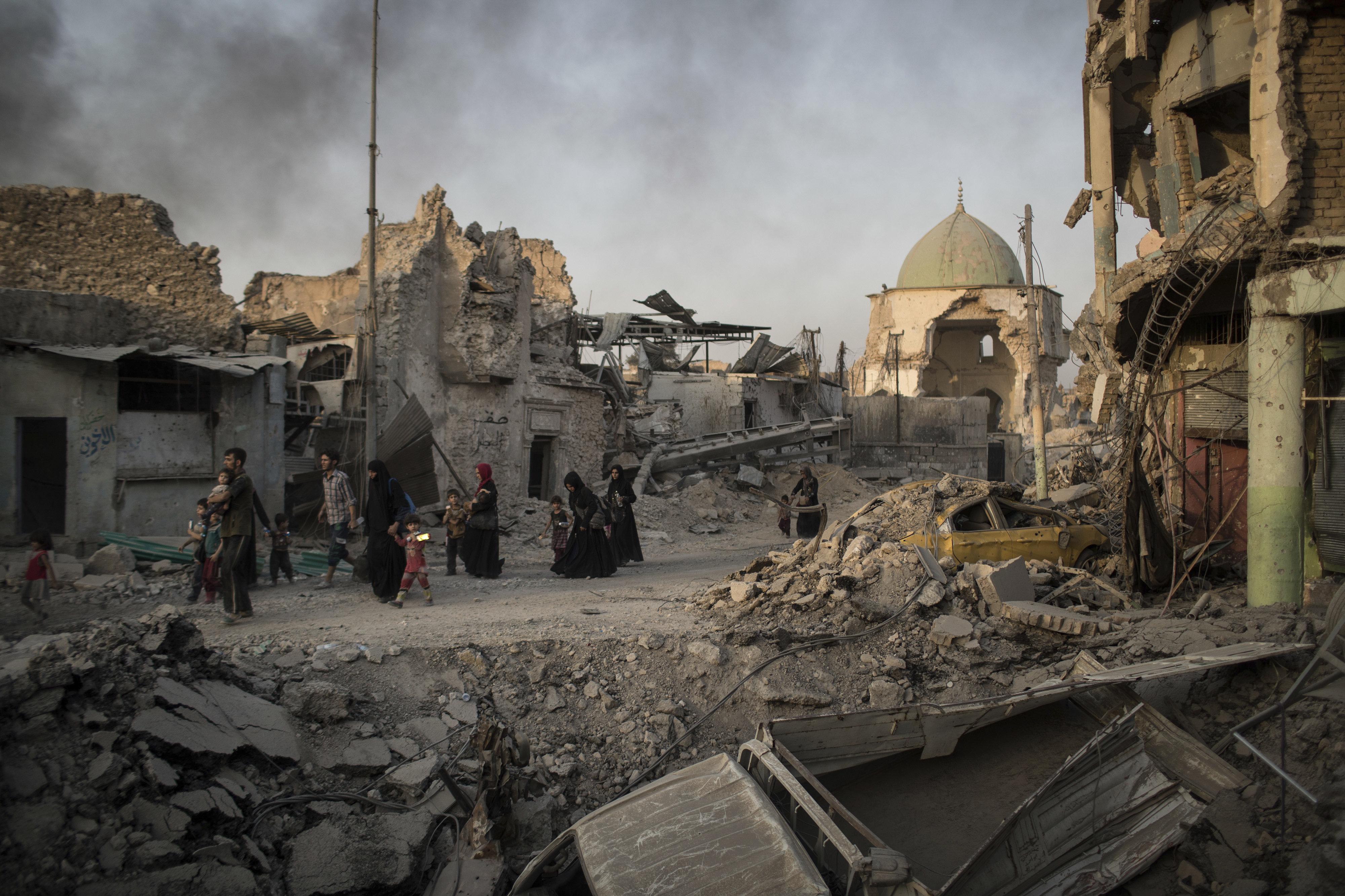 Civiles iraquíes pasan frente a la mezquita Al Nuri, muy dañada
