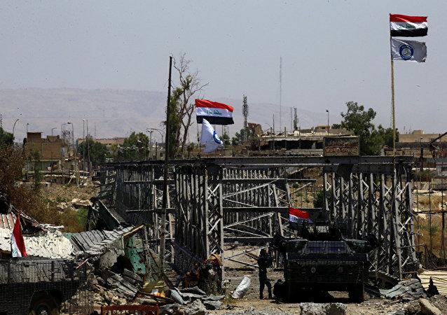 Un vehículo militar y las banderas de Irak cerca del puente destruido en Mosul (archivo)