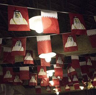 Las banderas de Catar con el retrato del emir, Tamim bin Hamad Thani