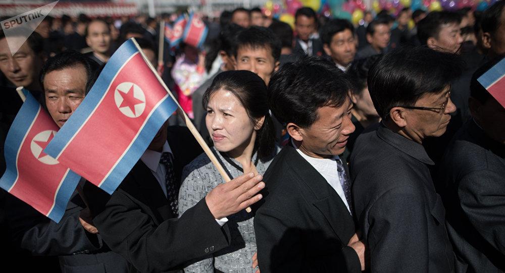 Los ciudadanos de Pyongyang con la bandera de Corea del Norte