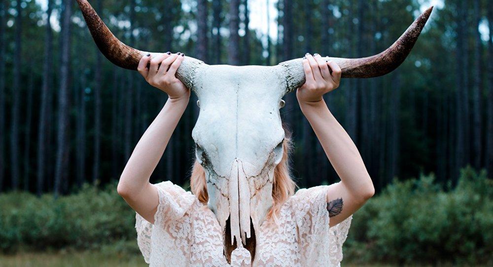 Una chica mantiene un cráneo de un animal