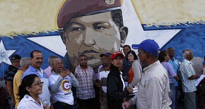 La gente venezolana ante una muralla con la imágen del expresidente de Venezuela, Hugo Chávez