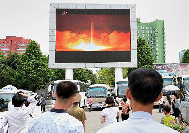 Personas observando el nuevo lanzamiento del misil en un estación de Pyongyang