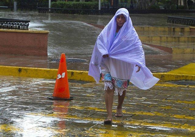 Una mujer se cubre de la lluvia tropical causada por el huracán Franklin