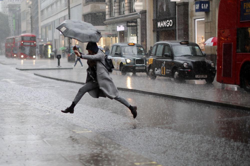 Una mujer salta sobre un charco en Londres