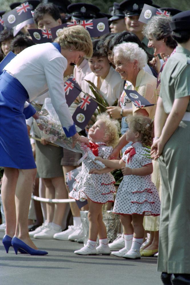 Hermanas gemelas regalan flores a la princesa Diana durante el último día de su gira asiática en Hong Kong, en 1989