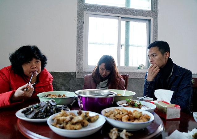 Zhao Yuqing cena con su cliente Wang Quanming y su madre