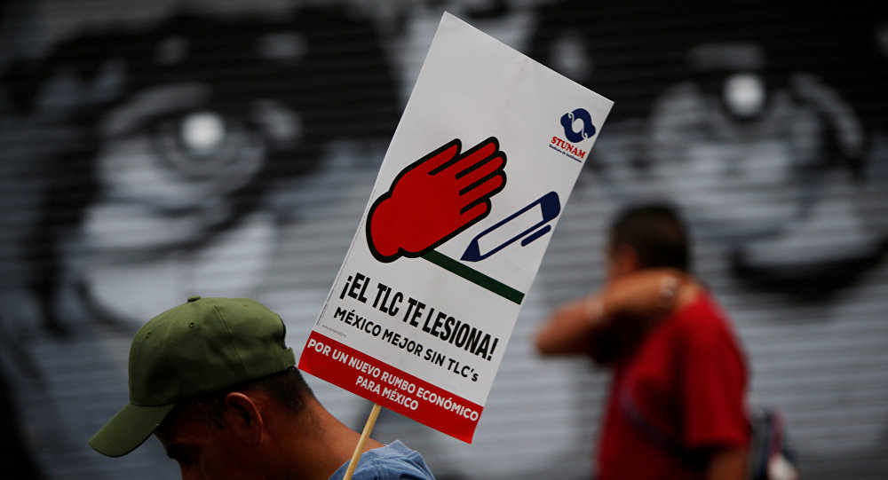 A man holds a placard during a protest with union workers and farmers as NAFTA renegotiation