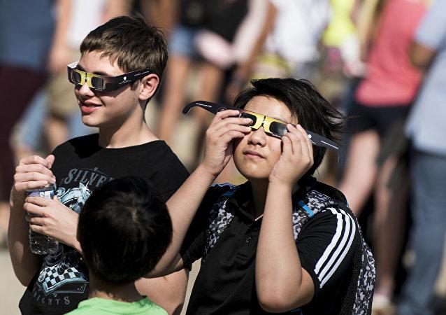 Niños prueban gafas con filtro solar antes del eclipse del Sol del 21 de agosto de 2017