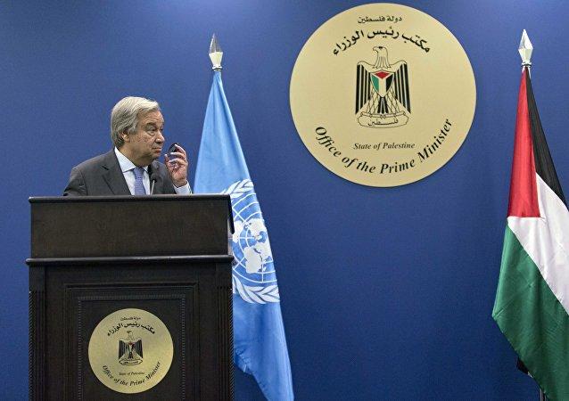 António Guterres, secretario general de la ONU, y las banderas de la ONU y Palestina