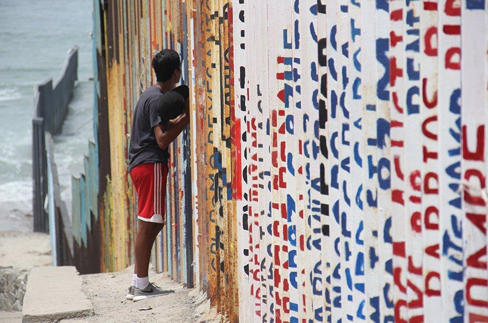 Un joven habla con sus familiares a través del muro que separa México y EEUU