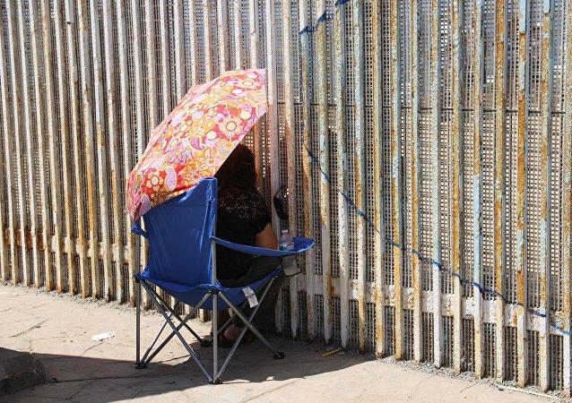 Una mujer habla con sus familiares a través del muro que separa México y EEUU (archivo)