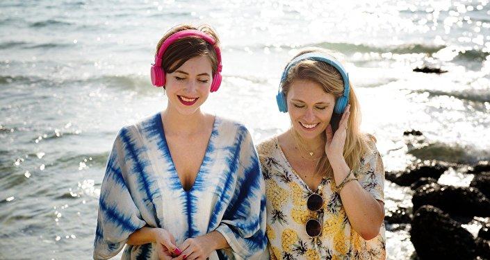 Unas chicas, escuchando música en la costa