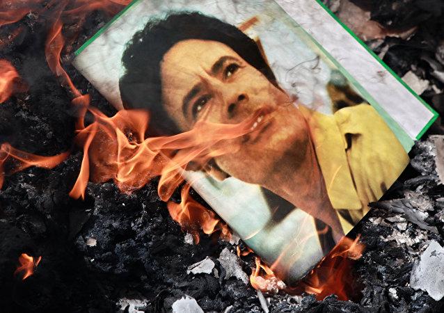 El retrato de Muamar Gadafi, quemado en la calle de Benghazi, Libia, en 2011