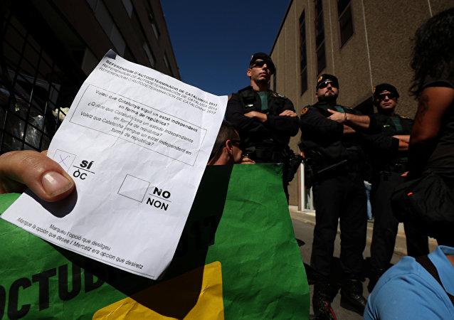 Un manifestante sujeta una papeleta del referéndum catalán frente a los agentes de la Guardia Civil