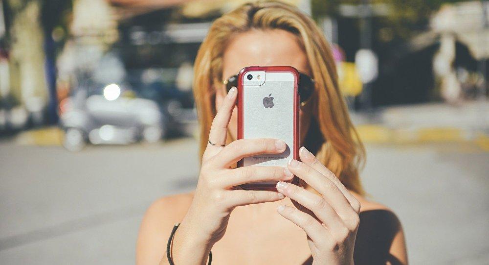 Una chica con un teléfono móvil iPhone de Apple