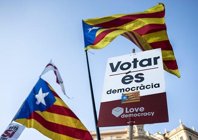 Las banderas de Cataluña junto con la carpeta diciendo Votar es democracia durante una manifestación a favor del referéndum independentista catalán (archivo)