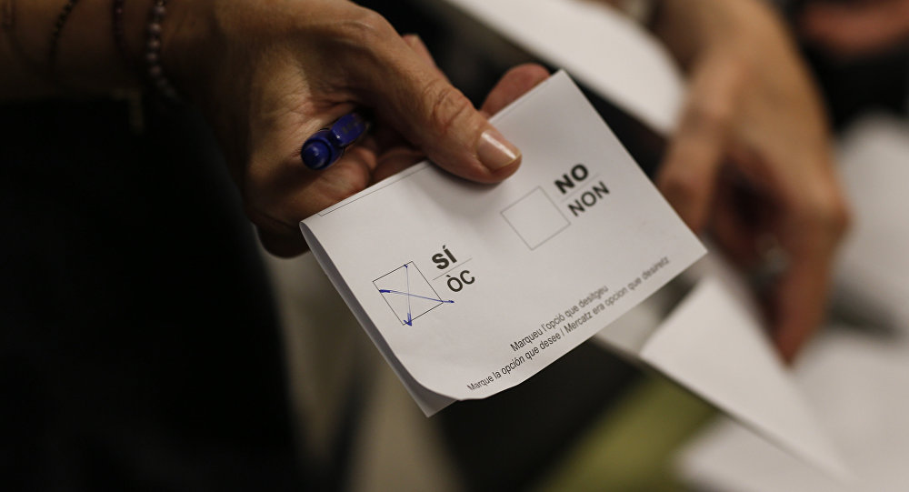 Una mujer muestra su boleta con la casilla Sí marcada en la Escuela Concepcio de Barcelona el 1 de octubre de 2017