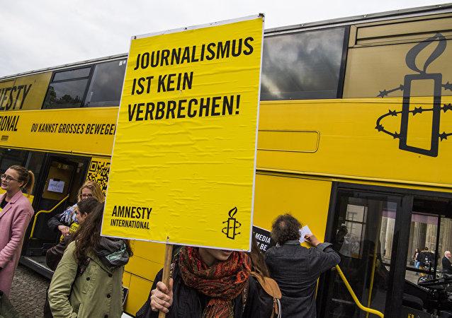 Una activista de Amnistía Internacional con un cartel: Periodismo no es crimen