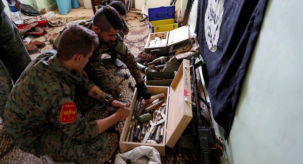 Los militares de Fuerzas Democráticas Sirias inspeccionan las armas de Daesh