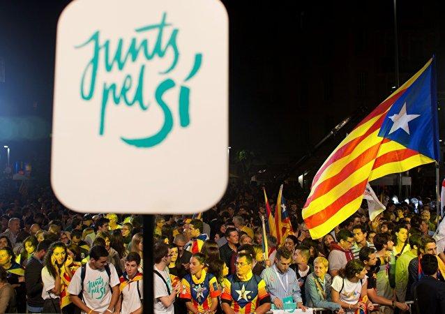 Catalanes con un cartel de Junts pel Sí y banderas catalanas