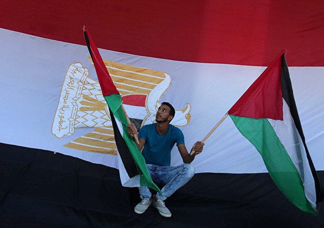 Un hombre con las banderas de Palestina y la bandera de Egipto al fondo