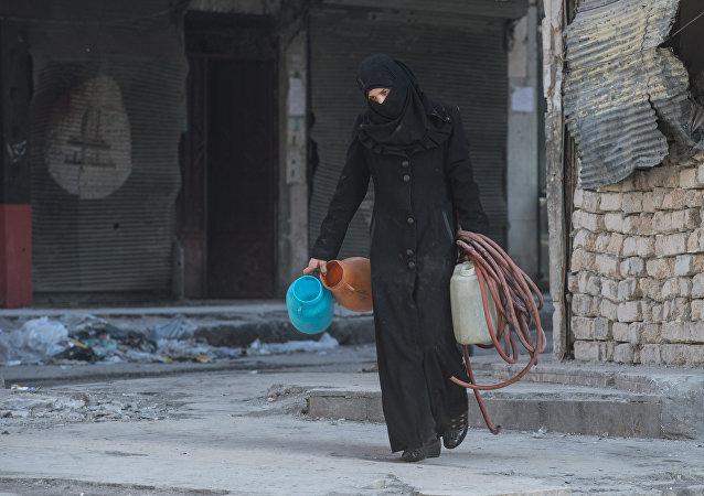 Una mujer camina en una zona residencial de una ciudad siria (imagen referencial)
