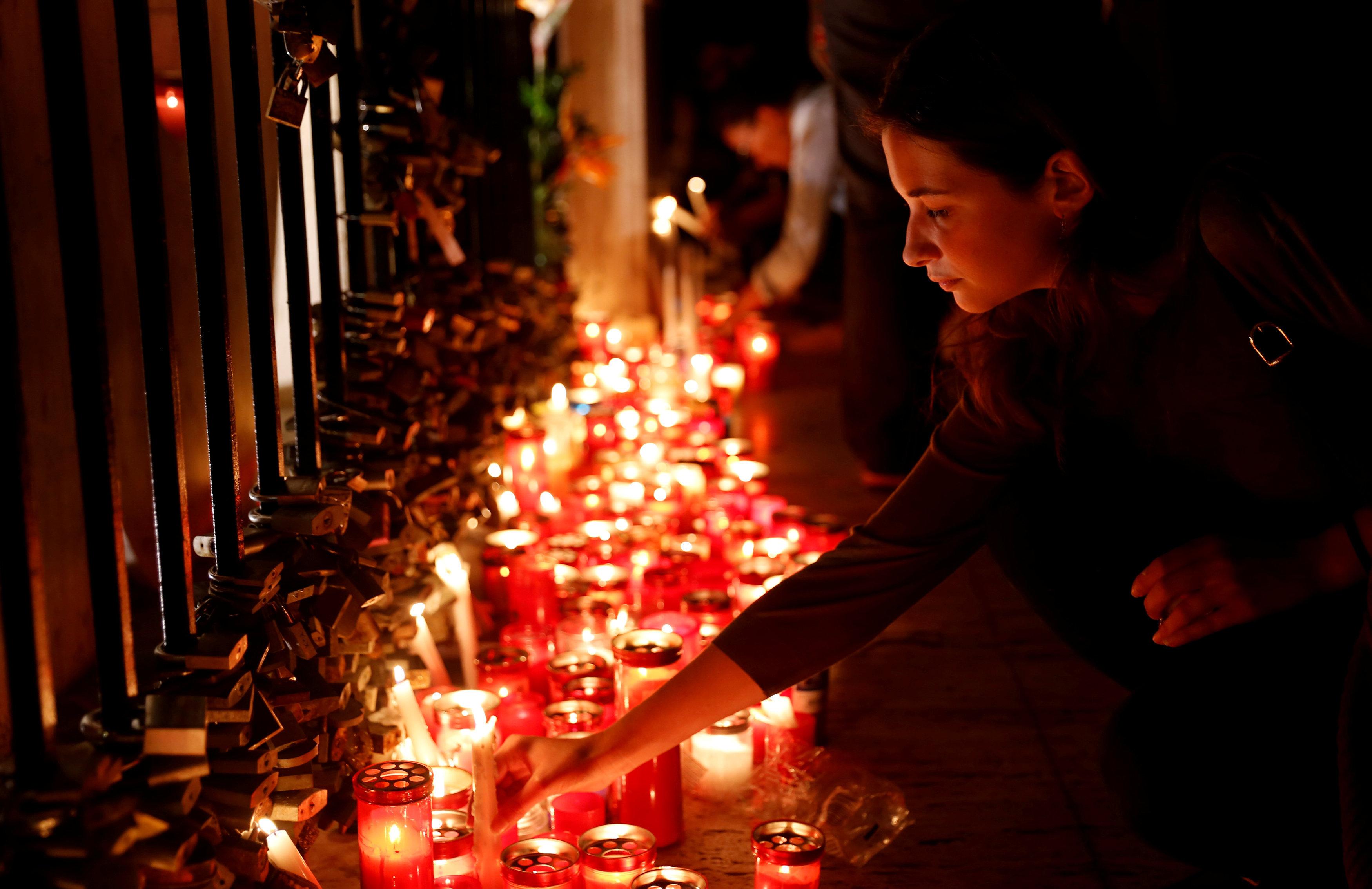 Una mujer ofrenda una vela en Malta tras el asesinato con coche bomba de la periodista de investigación Daphne Caruana Galizia en 16 de octubre de 2017