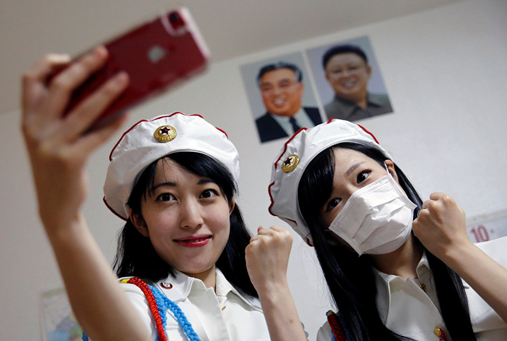 Chunhun (L), the leader of Japan's North Korea fan club called sengun-joshi, or military-first girls, poses for a selfie with another member in front of portraits of North Korea founder Kim Il Sung and late leader Kim Jong Il after their Moranbong Band dance practice in Tokyo, Japan October 22, 2017