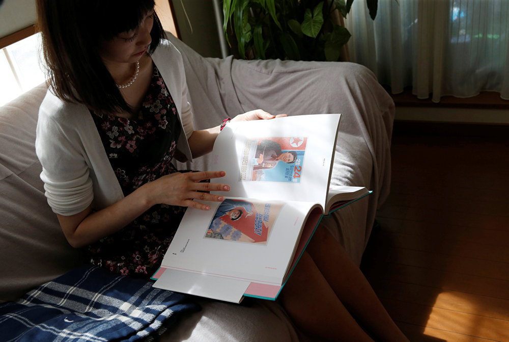 Chunhun, the leader of Japan's North Korea fan club called sengun-joshi, or military-first girls, looks at a photobook of North Korean art in Tokyo, Japan September 21, 2017. Picture taken September 21, 2017