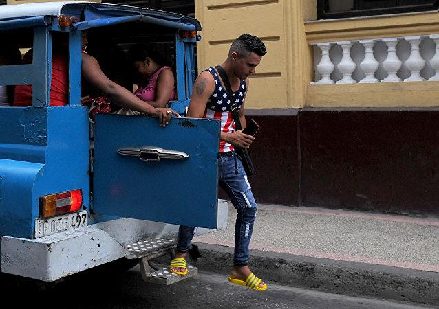 Un hombre, que lleva una camiseta de la bandera de EEUU, se baja de un vehículo en la Habana, Cuba