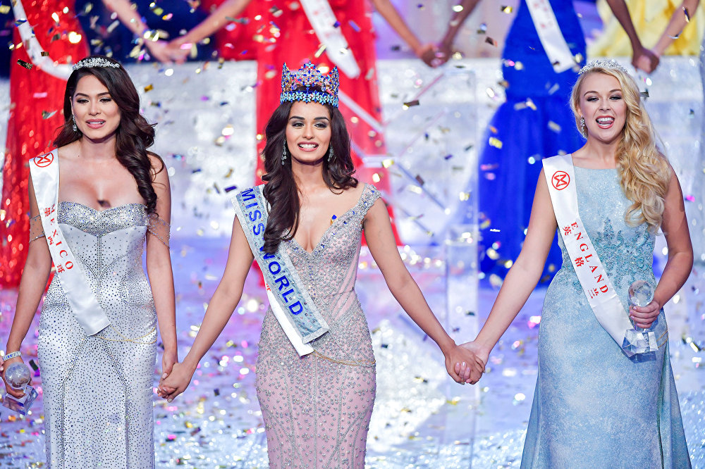 Winner of Miss World Miss India Manushi Chhillar holds hands with first runner-up Miss Mexico Andrea Meza and second runner-up Miss England Stephanie Hill at the Miss World pageant in Sanya