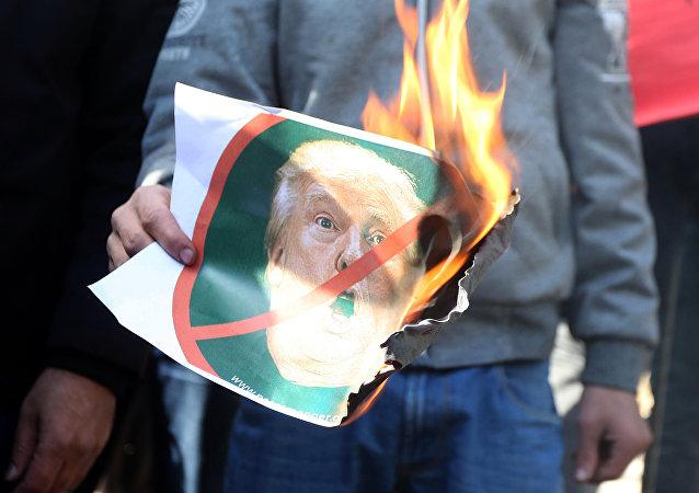 Protestante palestino con una foto de Donald Trump en llamas