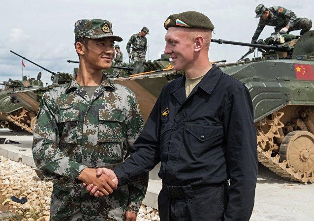 Soldado chino y soldado ruso se dan un apretón de manos durante Juegos Militares de Rusia