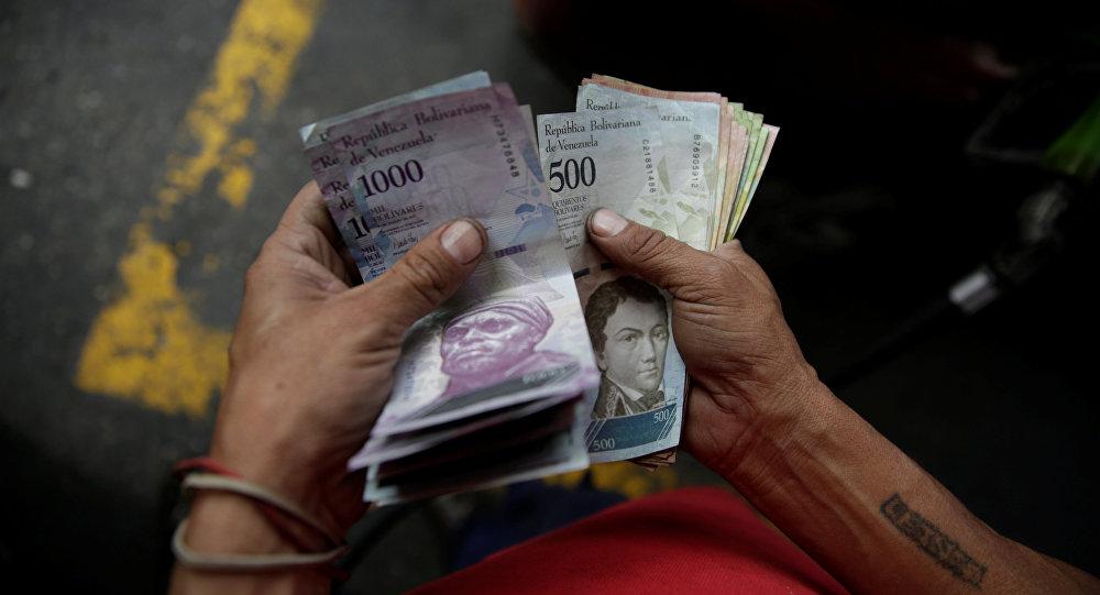 Un trabajador cuenta bolívares venezolanos en una gasolinera de la petrolera estatal venezolana PDVSA en Caracas