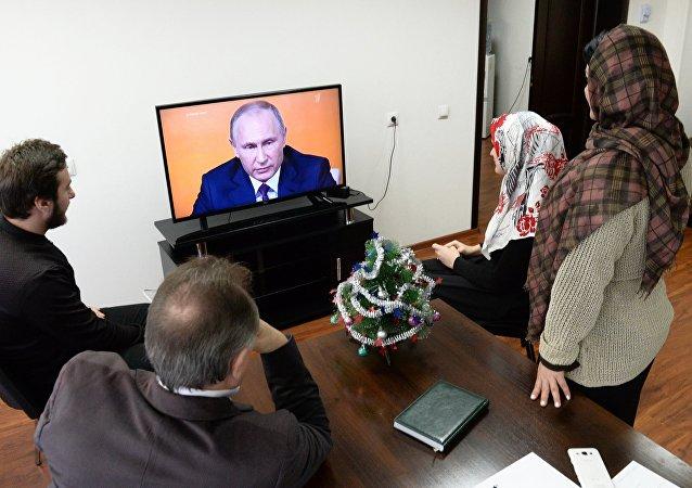Ciudadanos rusos ven por la televisión la gran rueda de prensa anual de Vladímir Putin