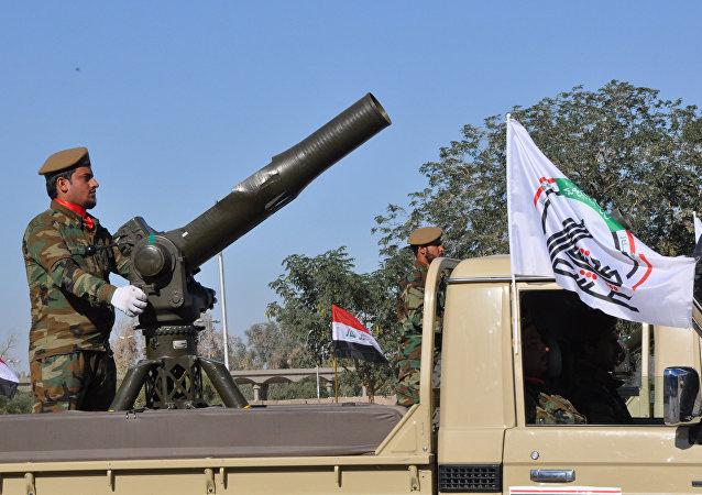 Un militante de las Fuerzas de Movilización Popular cerca de un cañón