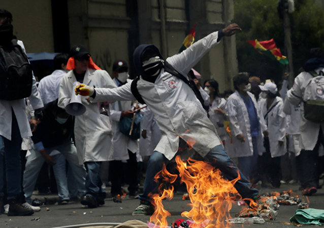 A demonstrator is seen during clashes with riot police as healthcare employees and students refuse new government policies about health system in La Paz, Bolivia