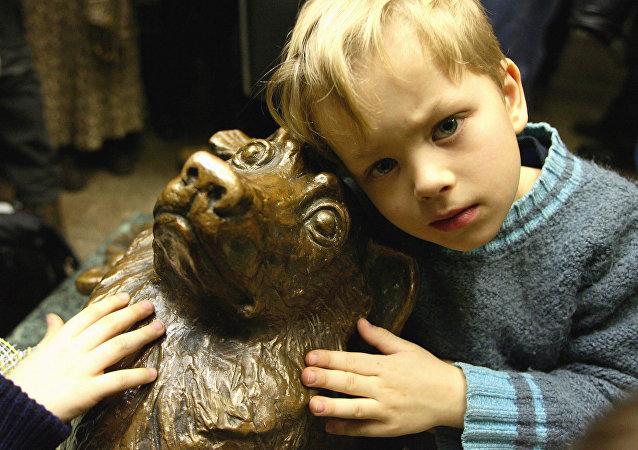 Un niño al lado de la estatua del perro Málchik en el metro de Moscú