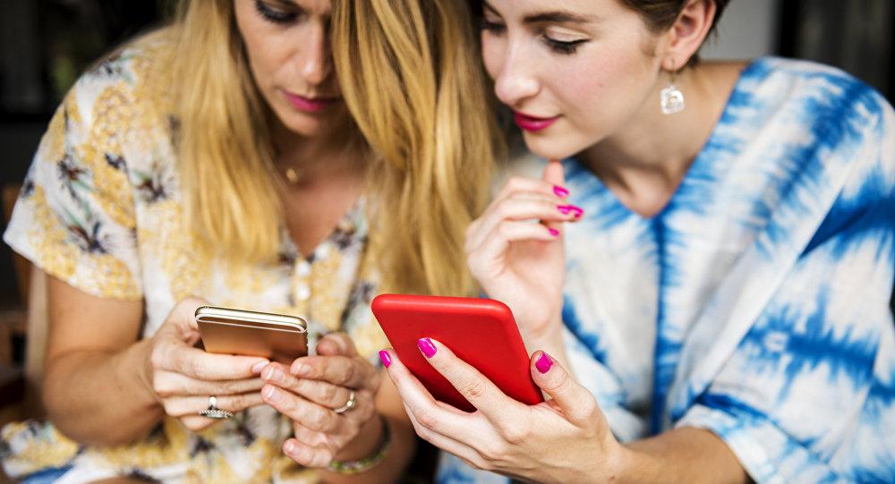 Dos mujeres con teléfonos móviles (imagen referencial)